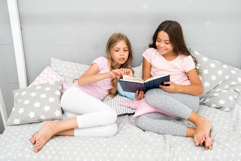 Children read book in bed. Family tradition. Girls best friends read fairy tale before sleep. Best books for kids stock photos