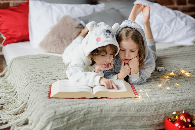 Two Children Lie On The Bed In Soft Pajamas. The Bedroom Is Decorated With  Christmas Lights. Children Read A Huge Book Of Christmas Stories. Merry  Christmas ...