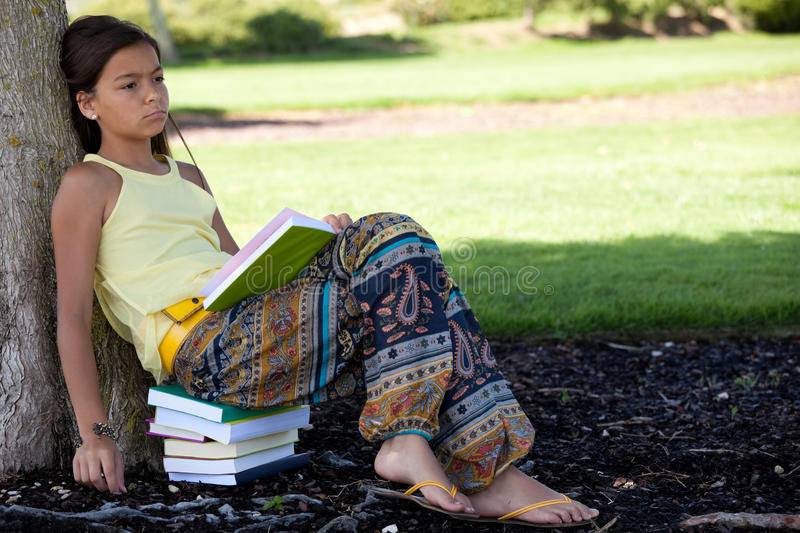 Children reading a book. Little girl relaxing next to a tree reading a book stock images