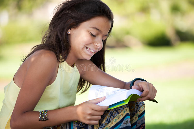 Children reading a book. Little girl relaxing next to a tree reading a book royalty free stock image