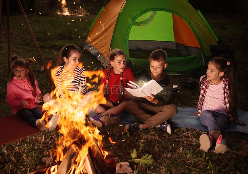 Children reading book with flashlight outdoors. Summer camp royalty free stock images