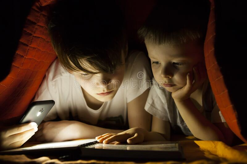 Children reading book with flashlight royalty free stock image