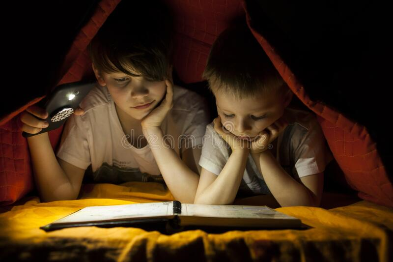 Children reading book with flashlight stock photography
