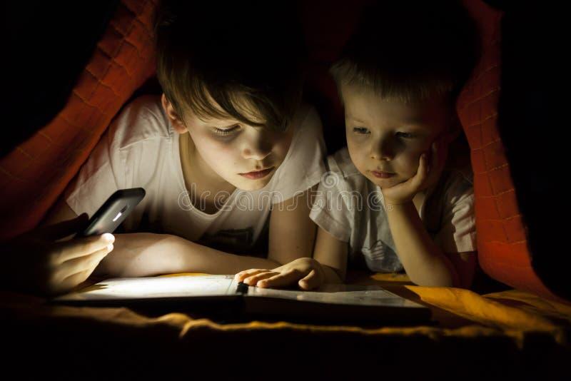 Children reading book with flashlight stock photo