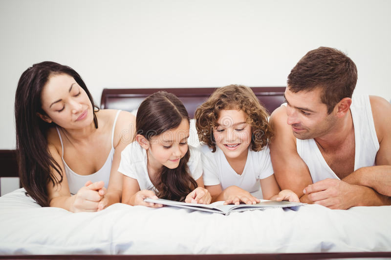 Children reading book with parents at home stock photography