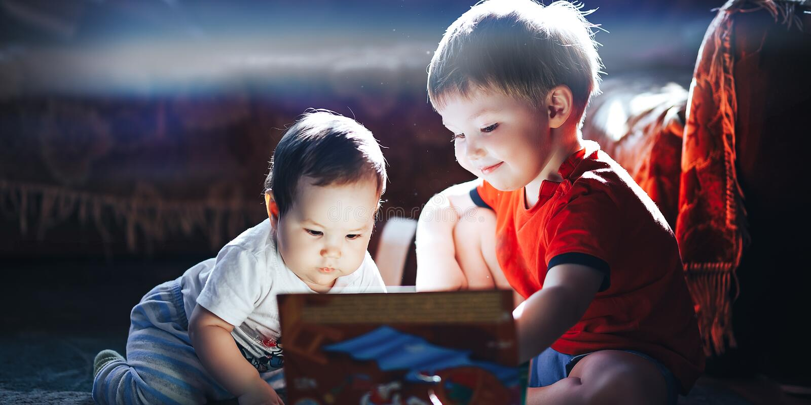 Children reading a book sitting together on floor at home. brother and babysister smiling having fun with book together. Boy and. Girl reading by the light of a stock photos