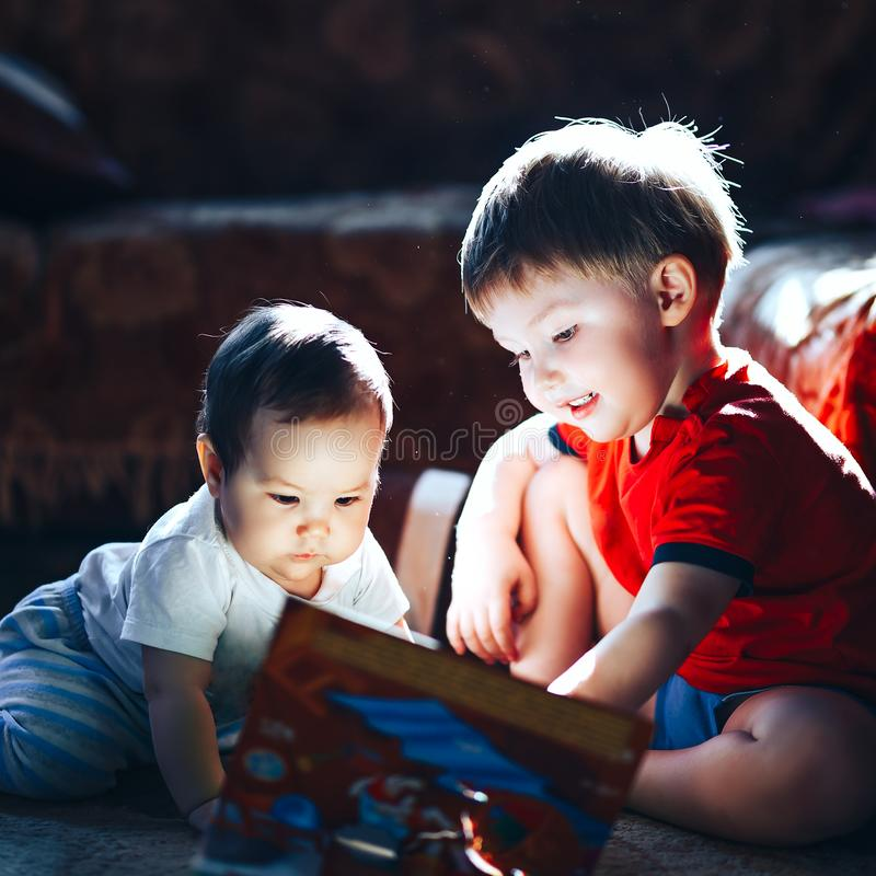 Children reading a book sitting together on floor at home. brother and babysister smiling having fun with book together. Boy and. Girl reading by the light of a royalty free stock photography