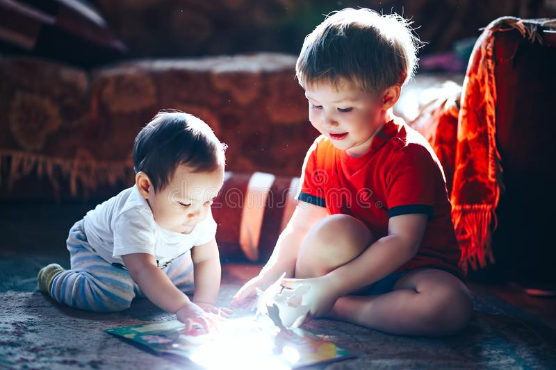 Children reading a book sitting together on floor at home. brother and babysister smiling having fun with book together. Boy and. Girl reading by the light of a stock image