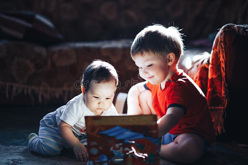 Children reading a book sitting together on floor at home. brother and babysister smiling having fun with book together. Boy and. Girl reading by the light of a royalty free stock photos