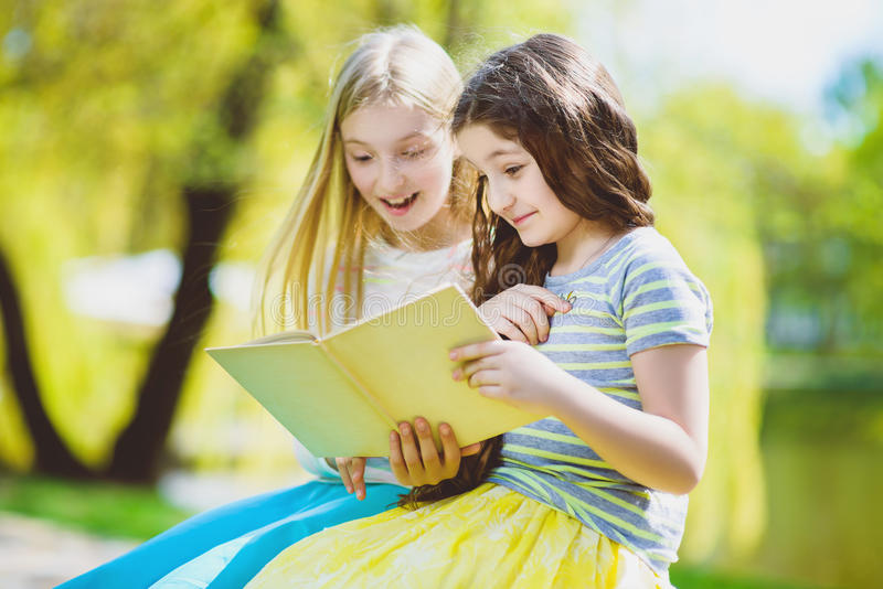 Children reading books at park. Girls sitting against trees and lake outdoor stock photography
