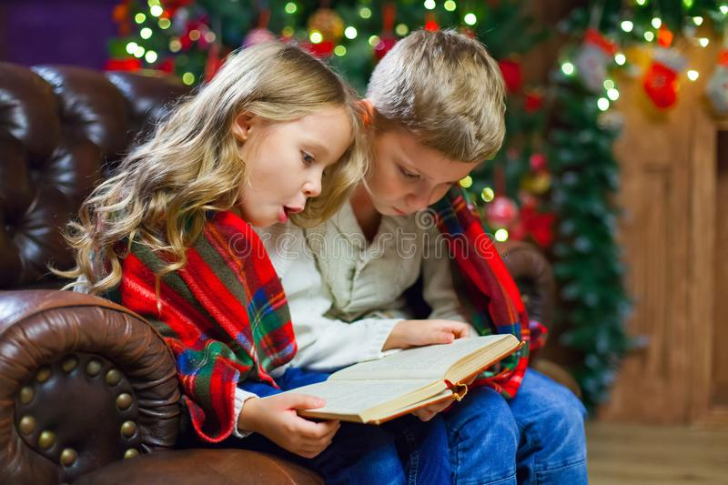 Children reading an interest book sitting on the bed against the stock images