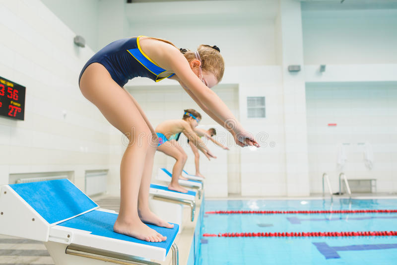 Children ready to jump into sport swimming pool. Sporty kids.  royalty free stock photography