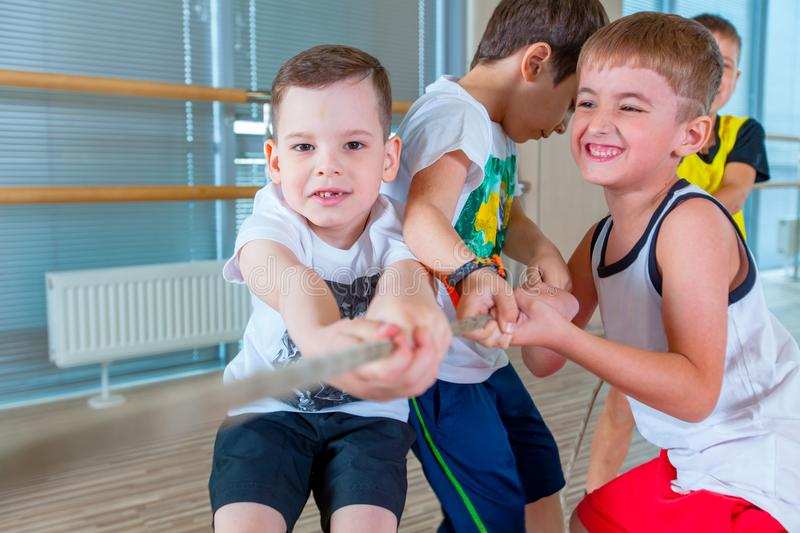 Children and recreation, group of happy multiethnic school kids playing tug-of-war with rope in gym royalty free stock images
