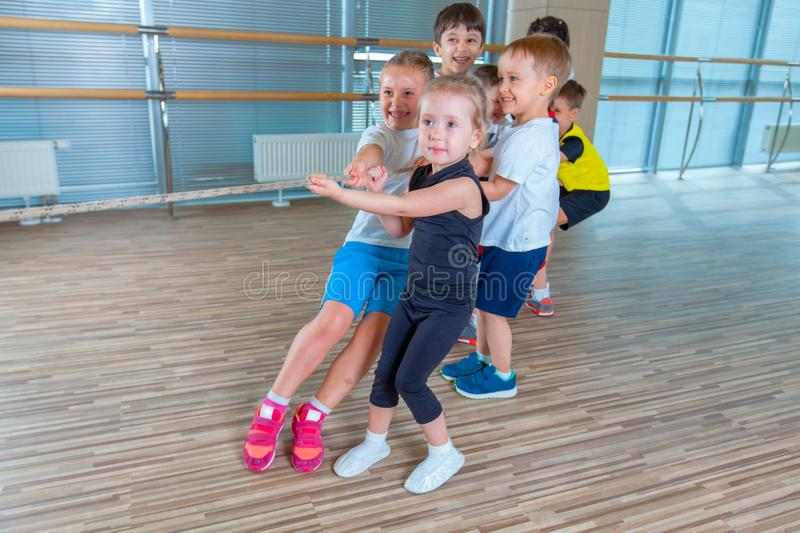 Children and recreation, group of happy multiethnic school kids playing tug-of-war with rope in gym stock photography