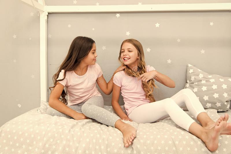 Children relax and having fun in evening. Sisters leisure. Girls in cute pajamas spend time together in bedroom. Sisters stock images