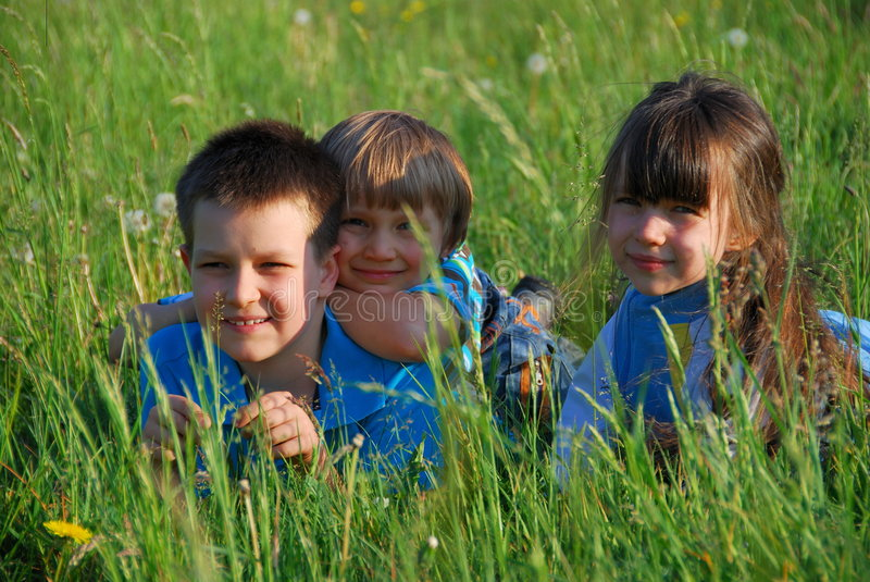 children relaxing in meadow stock image