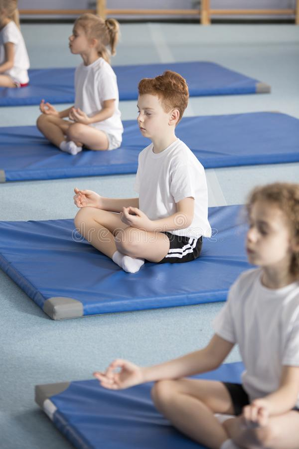 Children in relaxing meditation class. Elementary school pupil and other children sitting on mats with their legs crossed and eyes closed in relaxing meditation royalty free stock photo