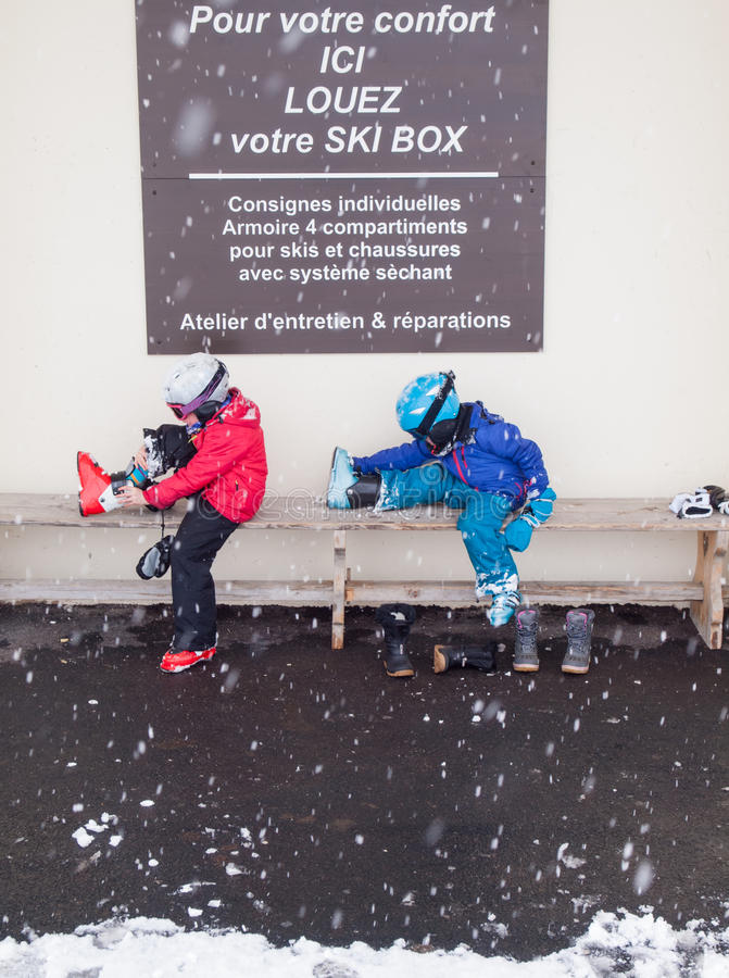 Children removing ski boots royalty free stock photography