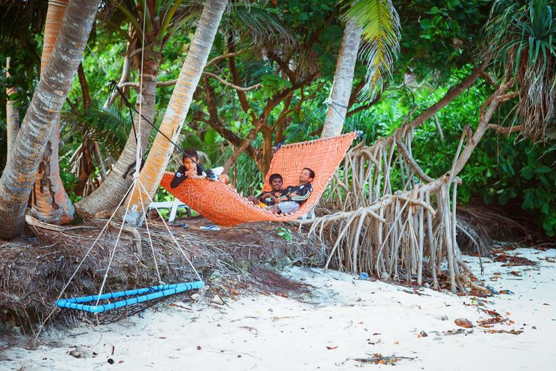 Children are resting in hammovk in the beach of island small village. Fuldhoo, Maldives - December 13, 2016: Children are resting in hammock in the beach of royalty free stock photos