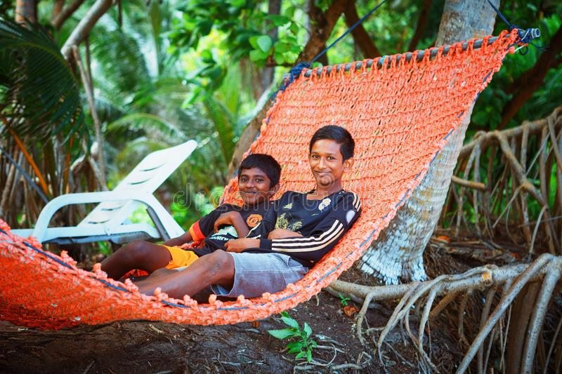 Children are resting in hammovk in the beach of island small village. Fuldhoo, Maldives - December 13, 2016: Children are resting in hammock in the beach of royalty free stock photography