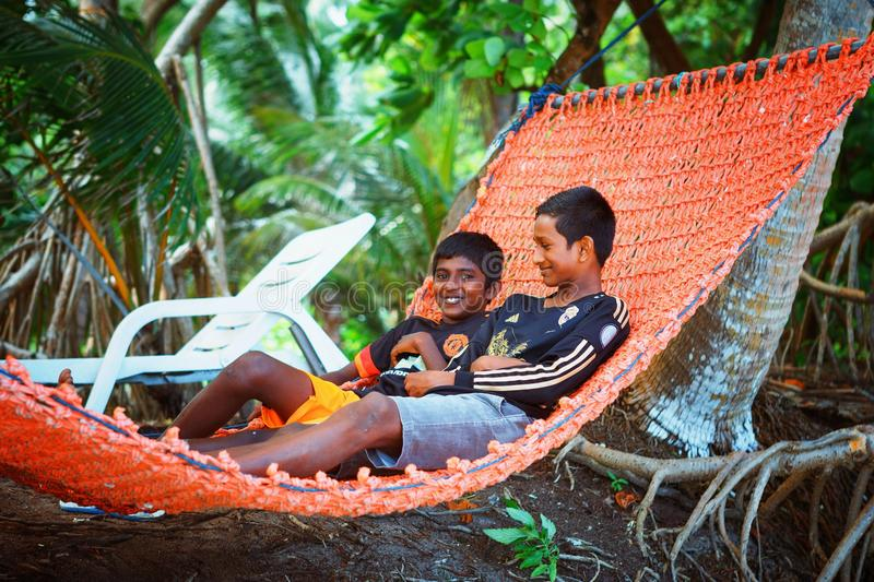Children are resting in hammovk in the beach of island small village. Fuldhoo, Maldives - December 13, 2016: Children are resting in hammock in the beach of royalty free stock images