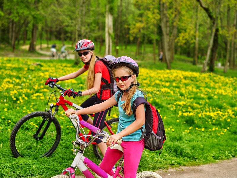 Children ride bicycle on green grass and flowers in park. Bikes bicyclist girl. Girls wearing bicycle helmet and glasses with rucksack rides bicycle. Bicyclist royalty free stock photos