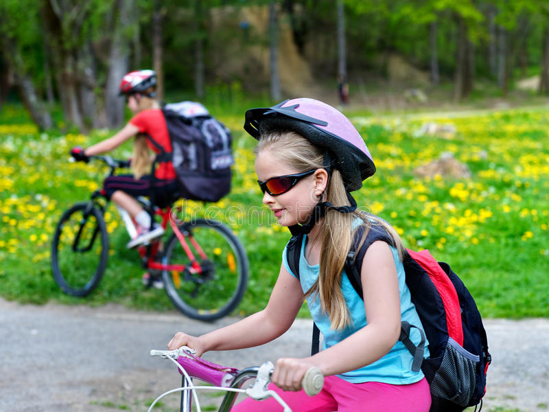 Children ride bicycle on green grass and flowers in park. Children wearing bicycle helmet and glasses with rucksack rides bicycle. Bicyclist children is looking royalty free stock photography