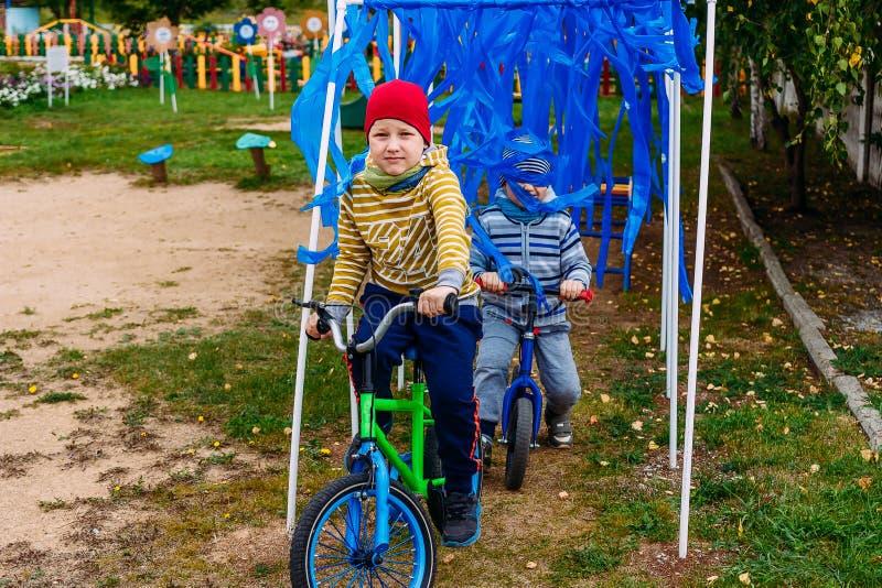 Children ride bikes in the playground. Happy Children ride bikes in the playground royalty free stock photography