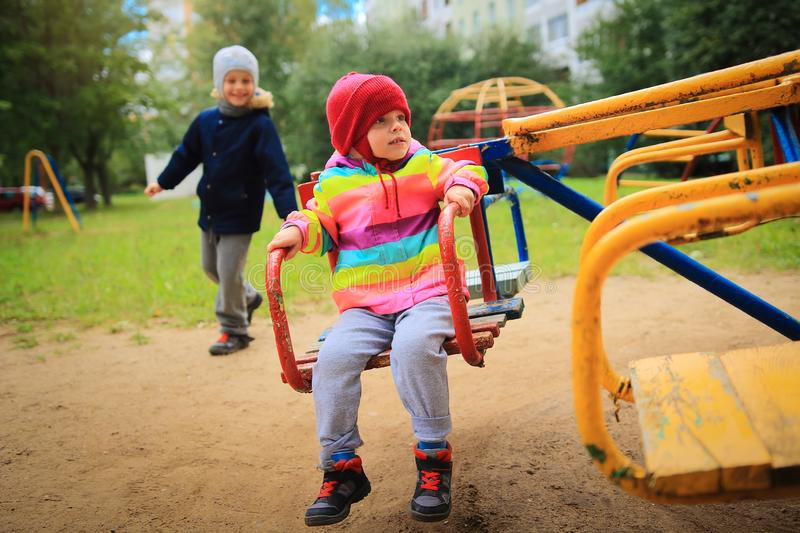 Children ride on the carousel in the playground. Playing children. Little cute babes ride on a swing. Children ride on the carousel in the playground. Playing royalty free stock image