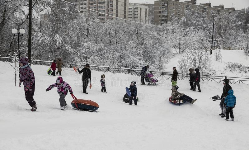 Children ride from the mountain on a snowy winter frosty day, Moscow royalty free stock photo