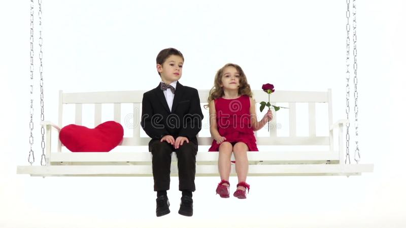 Children ride on a swing, they have a romantic relationship. White background. Slow motion. Children ride on a white swing, a little girl has a rose in her hand stock video footage