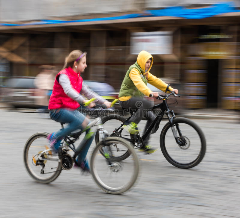 Children riding bicycles on a city street. Intentional motion blur stock photos