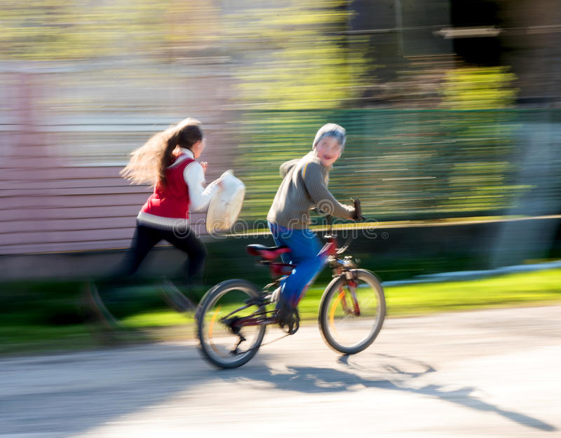 Children riding bicycles. On a city street. Intentional motion blur stock images