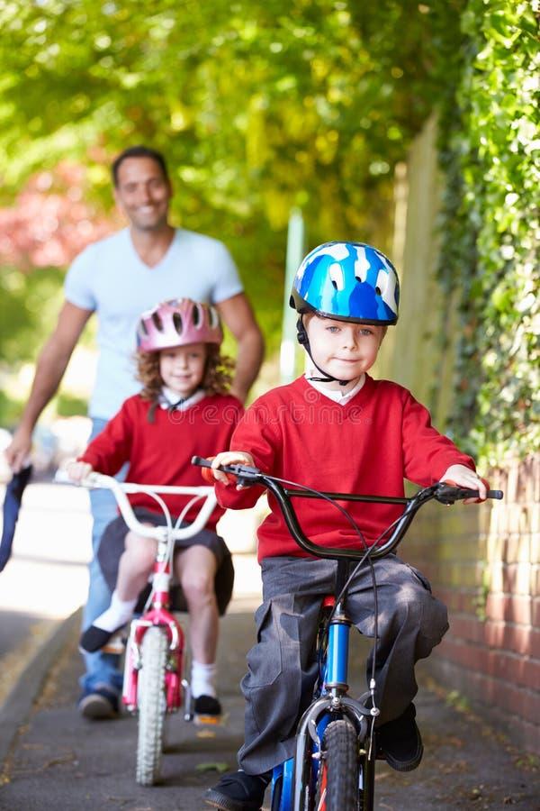 Children Riding Bikes On Their Way To School With Father. Children Riding Bikes On Their Way To School Wearing Helmets With Father Carrying Bag royalty free stock photos