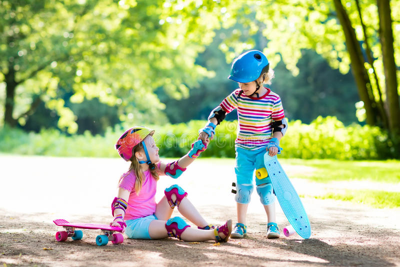 Children riding skateboard in summer park. Little girl and boy learn to ride skate board, help and support each other. Active outdoor sport for kids. Child royalty free stock image