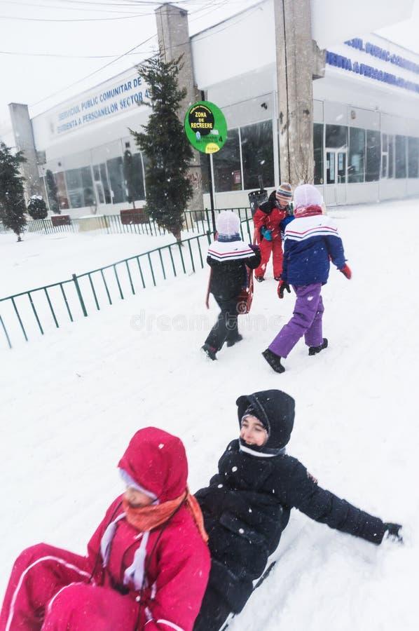 Children riding sleighs in Bucharest stock photography