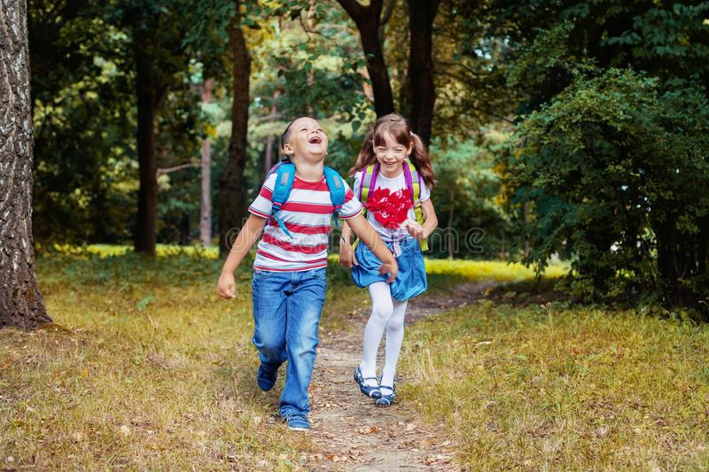 Children run with backpacks. Boy and girl. Back to school. The concept of education, school, childhood. Children run with backpacks. Back to school. The concept stock photo