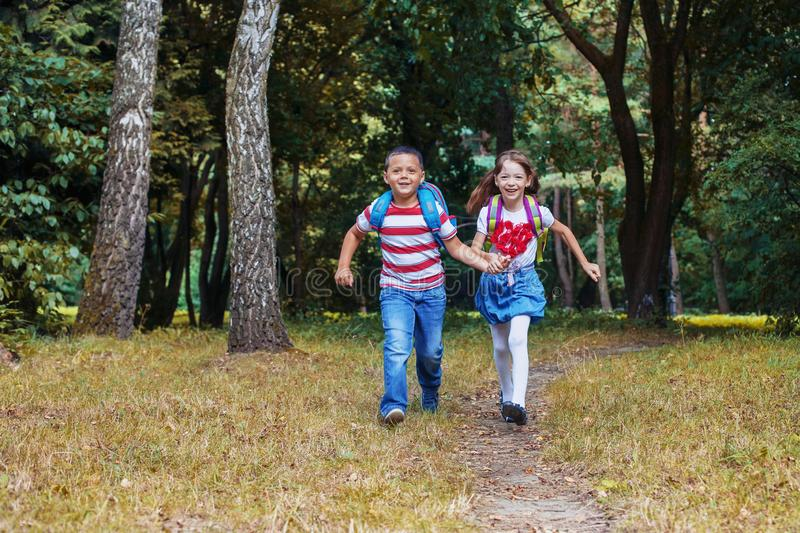 Children run with backpacks. Boy and girl. Back to school. The concept of education, school, childhood. Study royalty free stock images