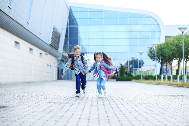 Children run with backpacks. The concept is back to school, study, friendship. Children run with backpacks. Little boy and girl. The concept is back to school stock images