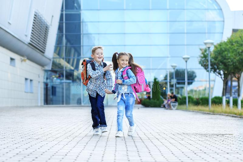 Children run with backpacks from school. The concept is back to school, study, friendship. Children run with backpacks from school. Little boy and girl. The stock photos
