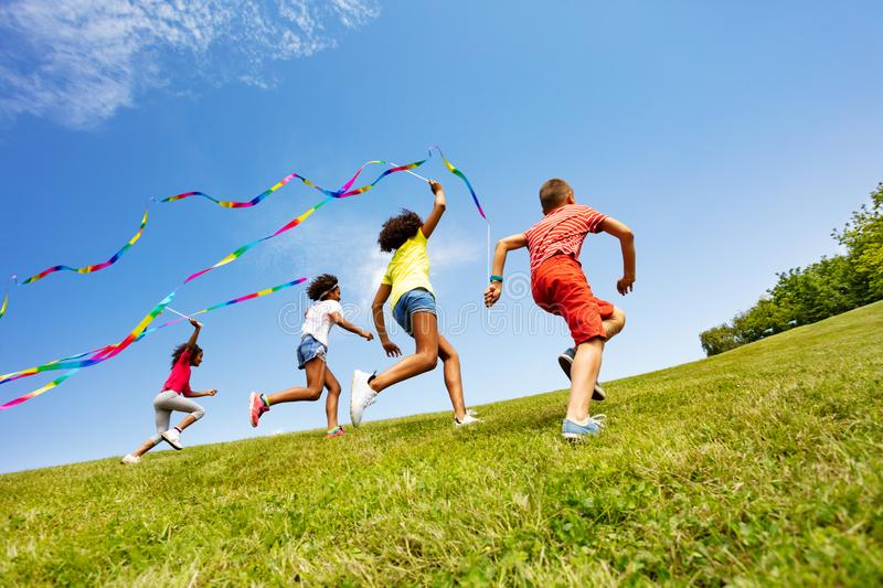 Children run colorful ribbons in park together. Group of children boy and girls run with colorful ribbons on the grass in park stock image