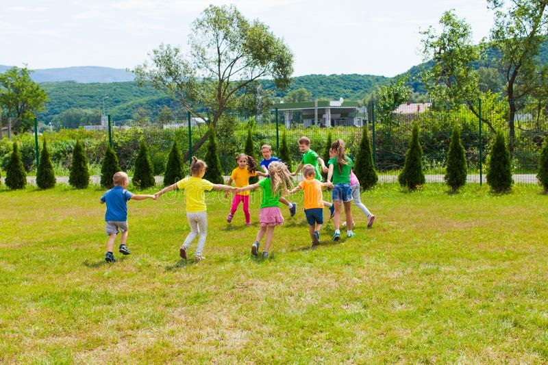 Children run holding hands on the green lawn royalty free stock photos