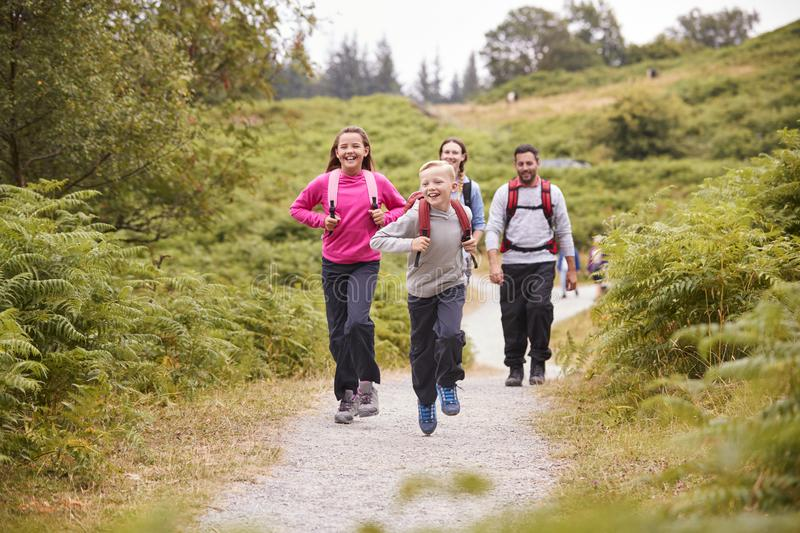 Children running ahead of parents walking on a country path during a family camping trip, selective focus stock image