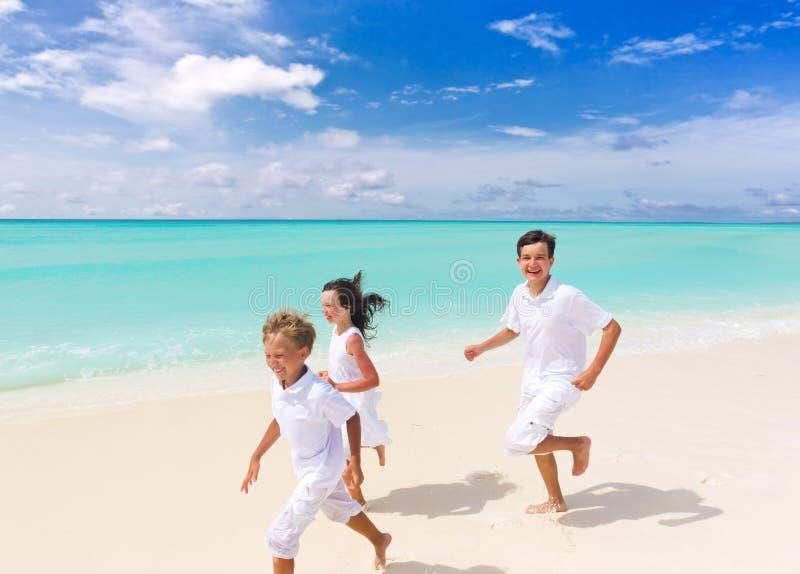 Children running on beach royalty free stock image