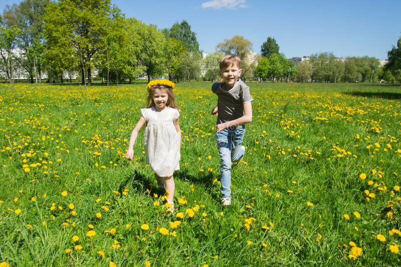 Children running in sunny meadow stock images