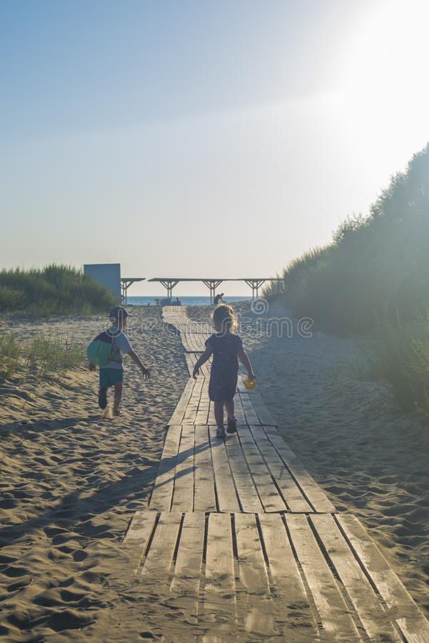 Children rush along the road to the sea in the evening, the view from the back. Anapa, resort on the black sea coast, Russia royalty free stock image