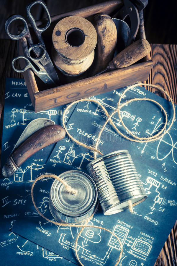 Children`s analog telephone made of string and cans. On old wooden table stock photography