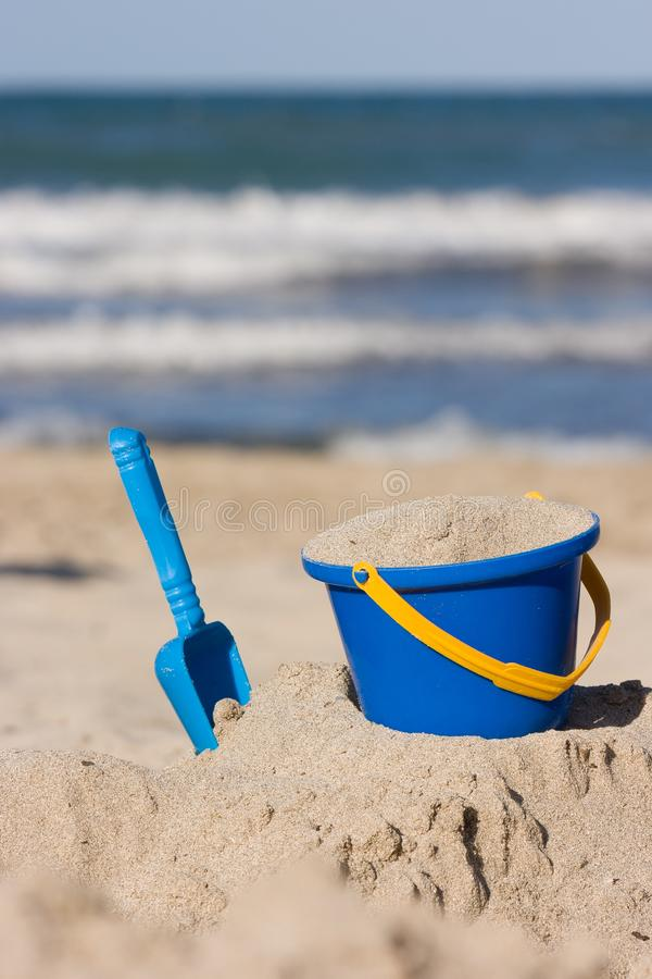 Children`s beach toys - bucket and shovel on sand on a sunny day. Outdoor kid`s activities at a beach with sea waves.  stock photos