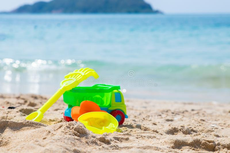 Children`s beach toys - buckets, spade, machine, car and shovel on sand on a sunny day. royalty free stock images