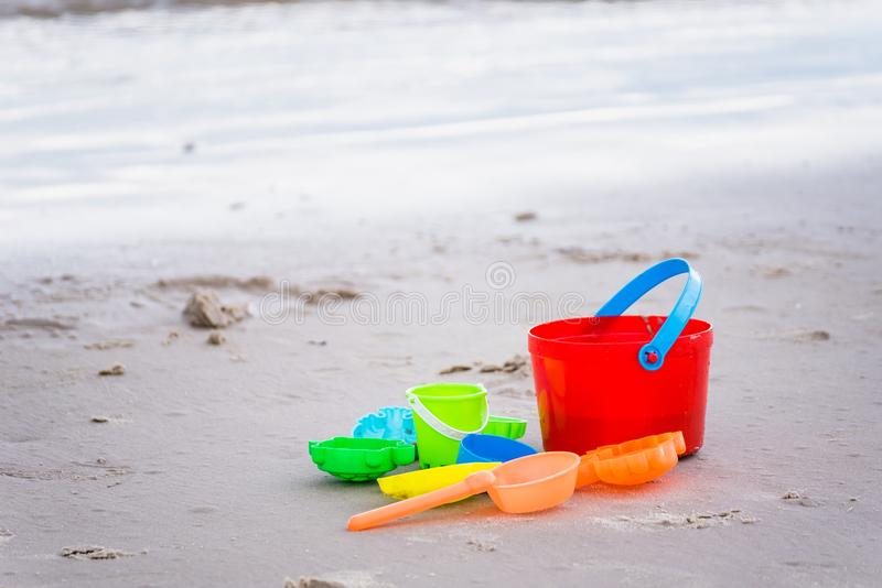 Children& x27;s beach toys - buckets, spade and shovel on sand on a s royalty free stock photography